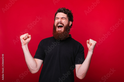 Fotografía  I won! Young bearded man making the winner gesture screaming on red background