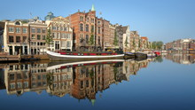 Crooked And Colorful Heritage Buildings And Houseboats, Overlooking Amstel River With Perfect Reflections, Amsterdam, Netherlands
