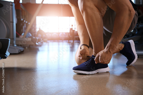 Obraz Sporty young man tying shoelaces in gym - fototapety do salonu