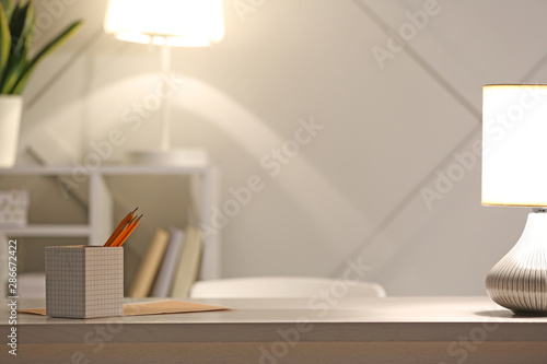 Obraz Workplace with glowing lamp in evening - fototapety do salonu