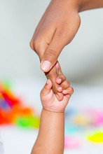A Asian Baby's Hand Holding Her Mother Finger