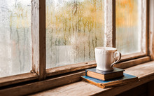 A White Cup And Old Books On The Background Of A Rustic Wooden Wet Window