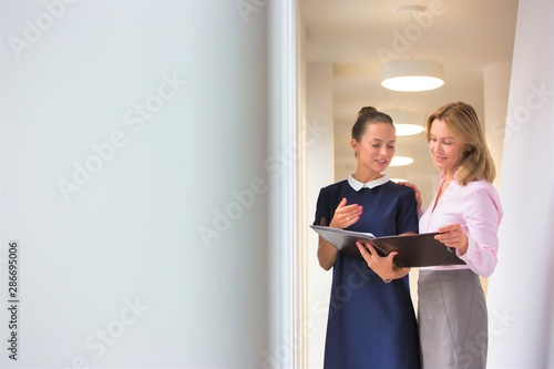Businesswomen discussing over document while standing in corridor at office