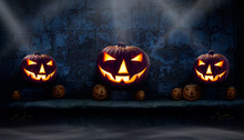 Three Lit Halloween Jack O Lanterns On The Left, Right And Centre On A Stone Plinth  At Night With Many Unlit Lanterns And Smoke Surrounding Them.