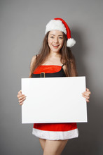 Beautiful Young Miss Santa Dressed In Christmas Costume Presenting Blank Sign With Copy Space