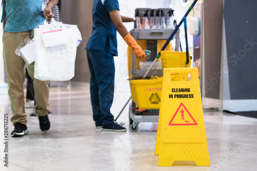 Fototapeta Janitor Cleaning Floor In Front Of Yellow Caution Cleaning in progress
