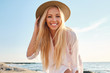 Leinwandbild Motiv Young attractive smiling blond woman in shirt and hat joyfully looking in camera with sea on background