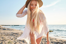 Young Joyful Blond Woman In Swimsuit And White Shirt Wearing Hat While Happily Looking In Camera With Sea On Background