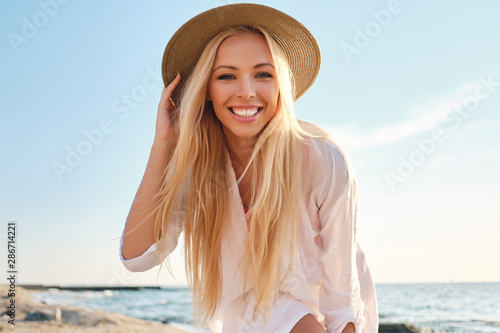 Young attractive smiling blond woman in shirt and hat joyfully looking in camera with sea on background - fototapety na wymiar