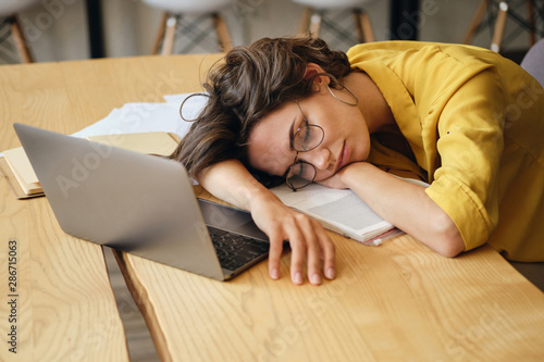 Young tired woman in eyeglasses asleep on desk with laptop and documents under h Canvas Print