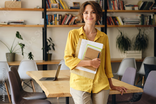Young smiling woman in yellow shirt leaning on desk with notepad and papers in hand while happily looking in camera in modern office