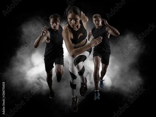 Fotografie, Obraz  Sporty young woman and men running