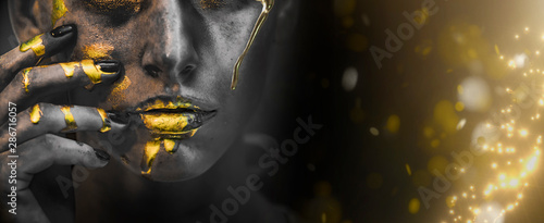 Gold Paint smudges drips from woman face, lips and hand, lipgloss   dripping from sexy lips, golden liquid drops on beautiful model girl's   mouth, gold metallic skin make-up Wallpaper Mural