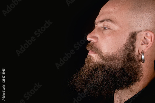 Fotografia  Bald and long beard hipster style man looking sideways in studio with black back