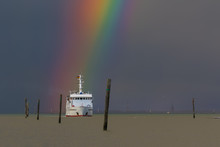 A Rainbow Over The North Sea Island Wangerooge. View From The Seaside Village Carolinensiel. A Ferry Is Just Coming From The Island. Dark Sky With The Colorful Colors Of The Rainbow.