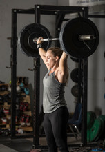 Strong Young Woman Lifting Hea...