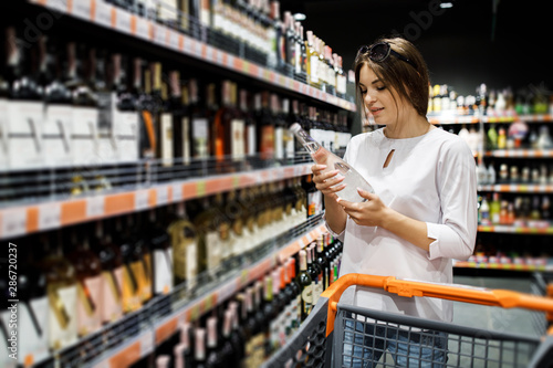 Fototapeta Young pretty girl is shopping in a big store. The girl buys groceries at the supermarket. Girl chooses drinks obraz