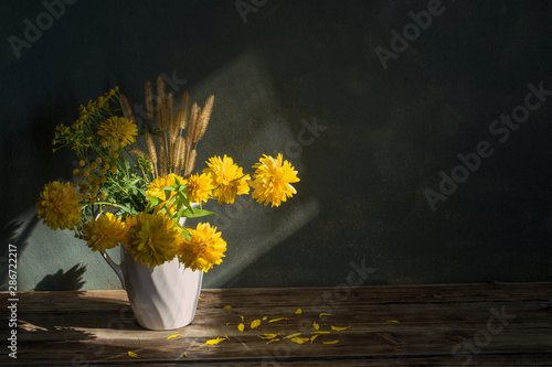 Fotomural yeliow flowers in white jug on dark background