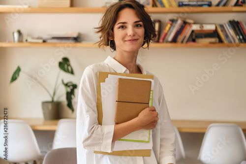 Obraz Young beautiful smiling woman dreamily looking in camera with papers and notepad in office - fototapety do salonu