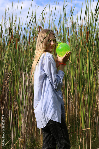 Cute blonde student girl posing with a round flask in her hands, with green fluorescent substance, against the background of tall, young reeds. Wall mural
