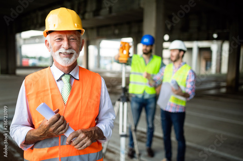 Fotografia  Engineer, foreman and worker discussing in building construction site