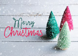 Fototapeta Konie - Merry Christmas text with trees and snow on wood background for holiday graphic banner.