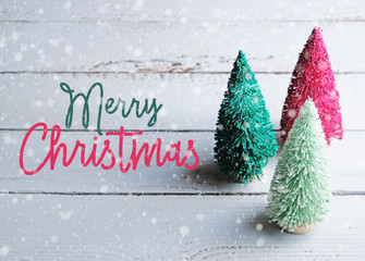 Merry Christmas text with trees and snow on wood background for holiday graphic banner.