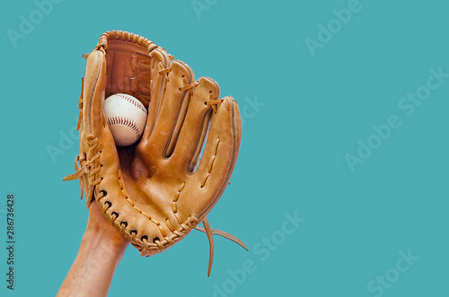 Fotografie, Tablou Hand in a leather baseball glove caught a ball on a green background