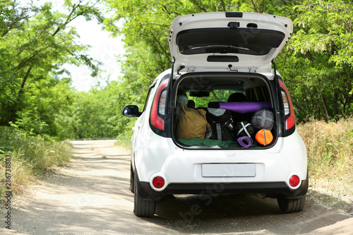 Fotografia, Obraz Car with camping equipment in trunk on forest road
