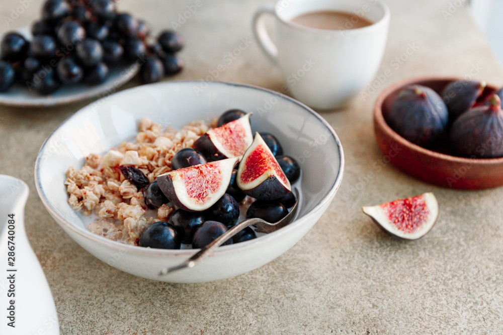 Fototapety, obrazy: Close-up view of a breakfast bowl with granola, blue grape and fig slices. Healthy vegan eating.