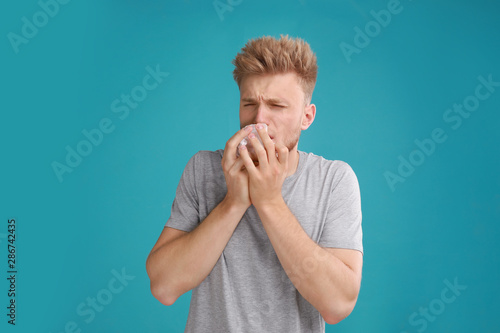 Foto  Young man suffering from allergy on blue background