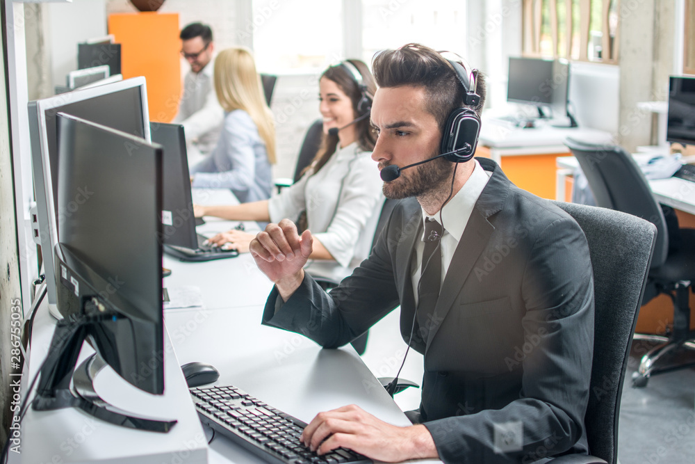 Fototapety, obrazy: Group of telephone operators working in call center.