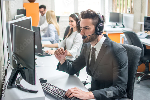 Group of telephone operators working in call center.