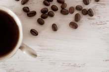 Flat View. Half A Coffee Cup With Coffee And Scattered Coffee Beans On A White Background. Place For Your Text.