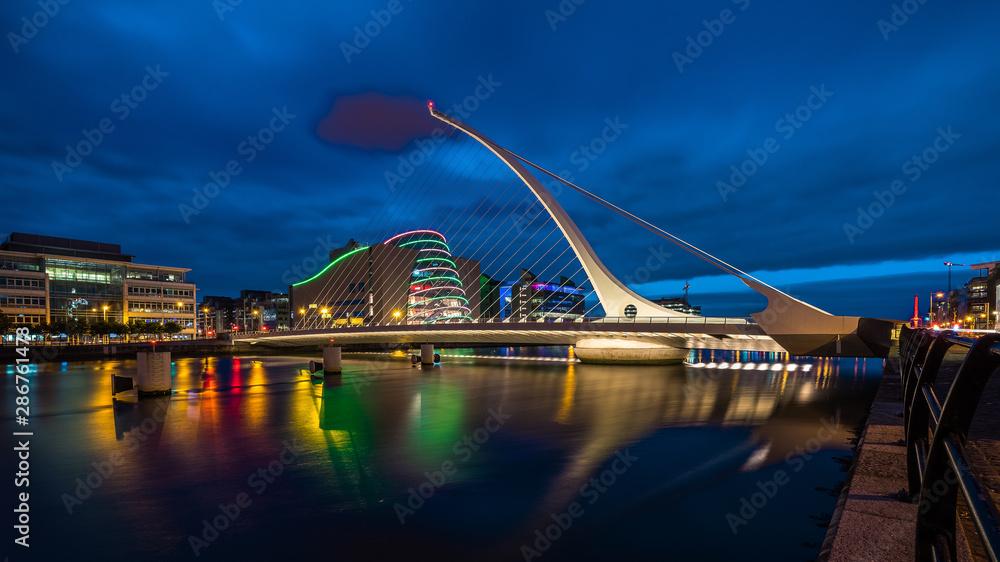 Fototapeta Samuel Becket Bridge at night in Dublin Ireland. Beautiful architecture and illuminated modern hotels