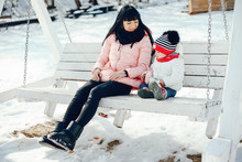 Family In A Winter Park. Elegant Woman In A Pink Jacket. Mother With Little Daughter Sitting On The Bench