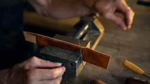 Man Sews Leather Details Clamped In Vice. Craftsman Works With Needle And Thread. Small Business Concept.