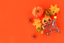 Halloween Shopping Holiday Concept / Accessories With Spider Pumpkin Jack O Lantern And Leaves Autumn In A Shopping Cart On Orange Background Top View Aerial Image Flat Lay Copy Space