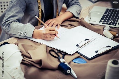 Closeup of attractive female fashion designer hand working in home office workshop Fototapeta