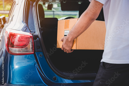 Obraz na plátně Delivery man is delivering cardboard box to customers via private car trunk door