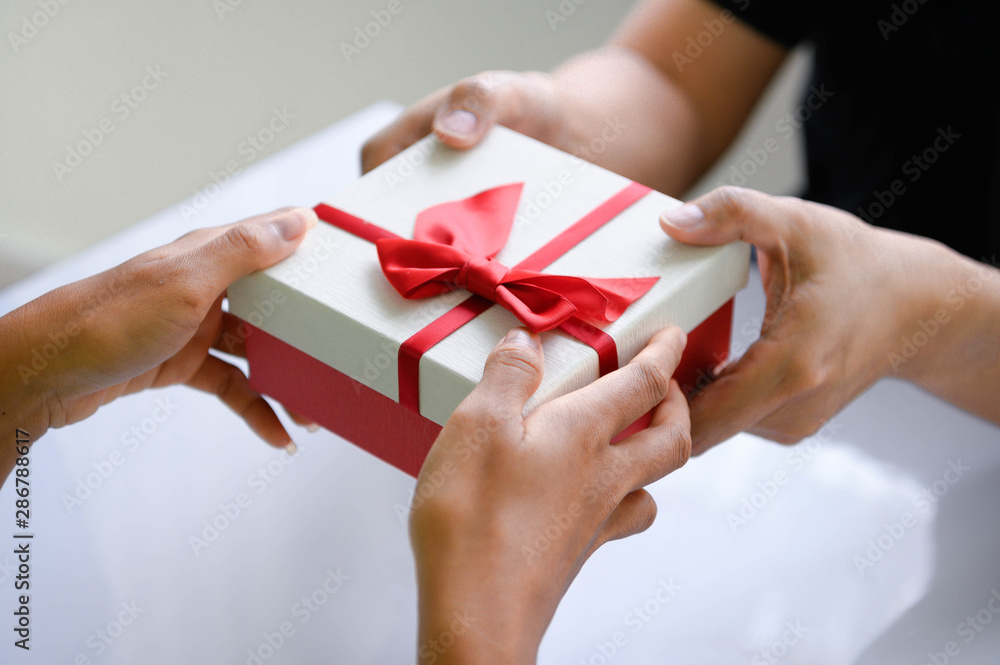 Fototapeta Closeup of hands giving gift box in Christmas day and new year festival to each other. Holiday and event. Surprising giftbox in dating on end year party. People lifestyle and object concept.