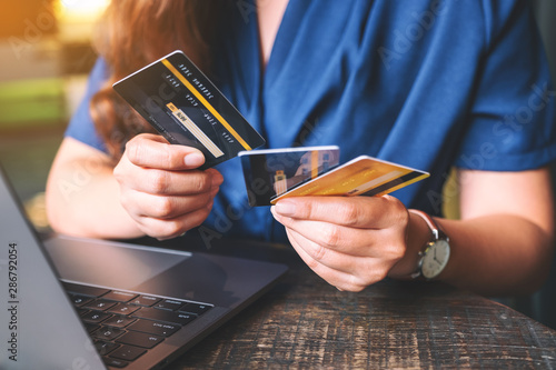 Fototapeta Closeup image of a woman holding and choosing credit cards while using laptop computer obraz