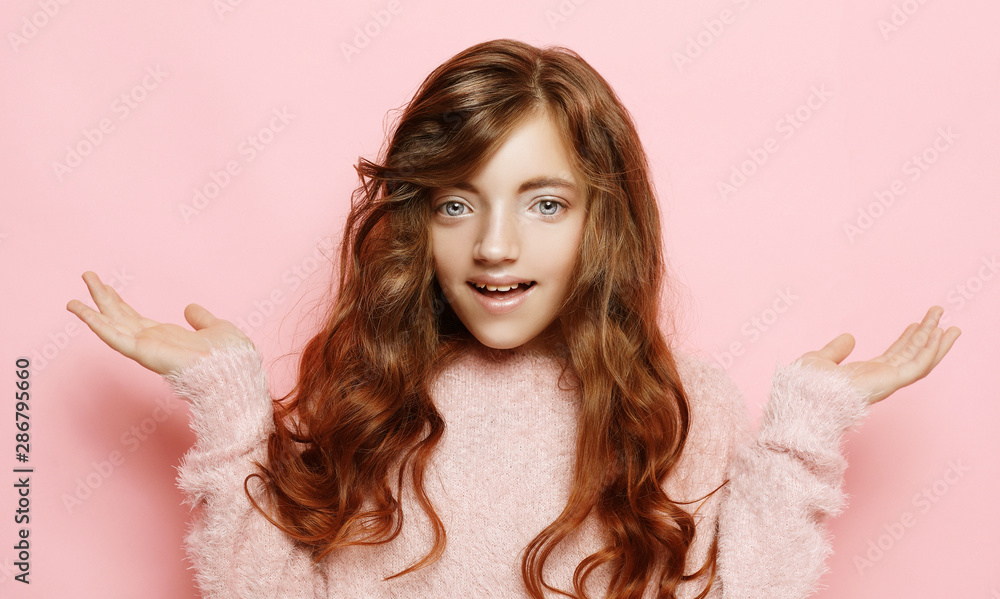Fototapeta beautiful curly girl in casual clothes looking camera and smiling isolated over pink background