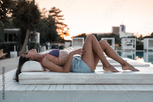 Fototapeta A girl with long legs and a sports body is resting and lying near the pool in a fashionable hotel. obraz na płótnie