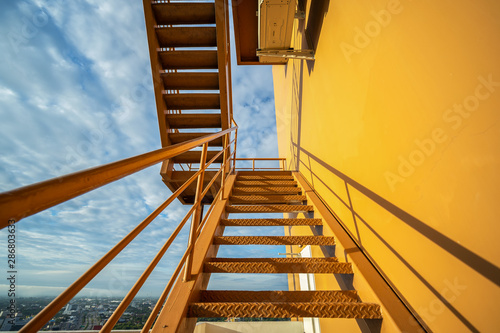 Valokuvatapetti Fire escape stairs mounted to the outside, Emergency exit with yellow wall