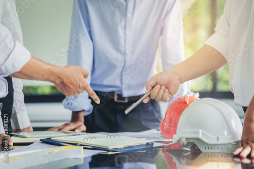 Contractor and engineer with blueprints discuss at a modern construction site, E Canvas Print