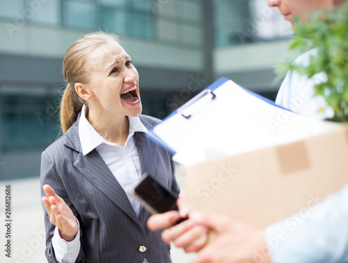 Photo Irate woman is dismissing young manager for violating the job description
