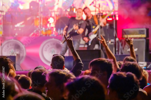 Fans cheering musicians on stage at live rock music concert