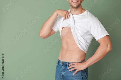Photo Handsome muscular man on color background. Weight loss concept