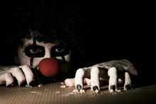 A Terrible Creepy Clown Peeps Out Of The Basement And Scratches The Floor With His Claws.